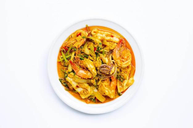 Smażone owoce morza z curry w proszku na białym tle