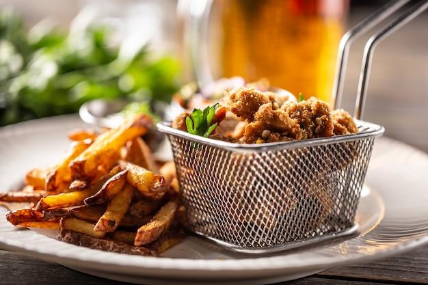 Smażone panierowane nuggetsy z kurczaka z frytkami podawane na talerzu.