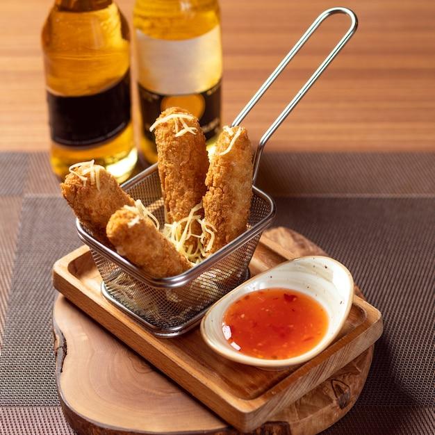Smażone panierowane paluszki z kurczaka z sosem pomidorowym z butelką piwa