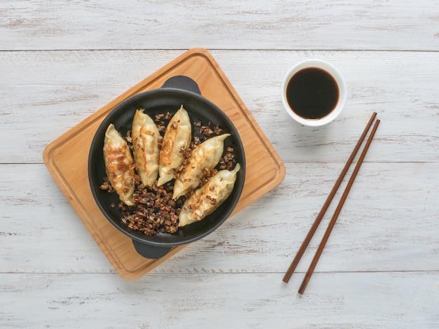 Smażone pierogi gyoza na patelni, sosie sojowym i pałeczkami