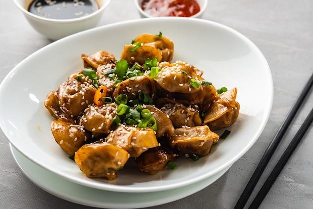 Smażone pierogi z sosem sojowym z pieprzem i zieloną cebulą. kuchnia azjatycka