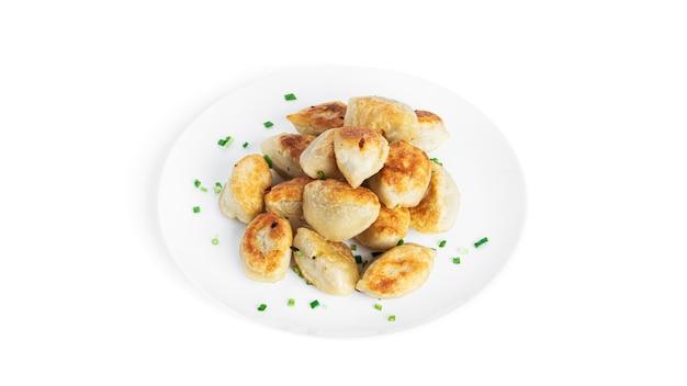 Smażone pierogi z ziemniakami i zieloną cebulką na białym tle.