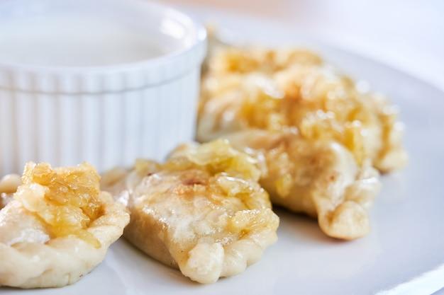 Smażone pierożki nadziewane mięsem posypane karmelizowaną cebulą na białym talerzu