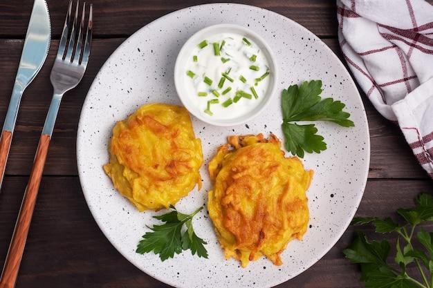 Smażone placki z tartych ziemniaków na talerzu z sosem