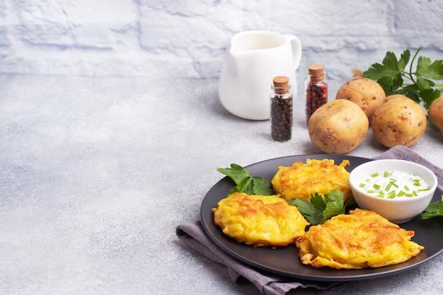 Smażone placki z tartych ziemniaków z sosem.