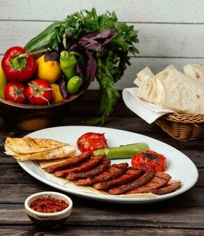 Smażone plastry mięsa z pieczonymi warzywami na drewnianym stole