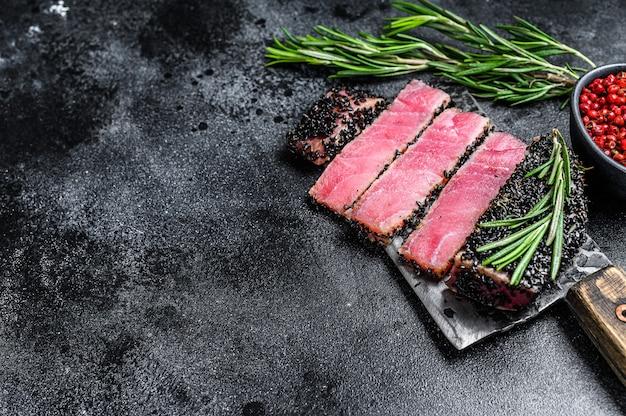 Smażone plastry stek z tuńczyka rybnego na tasaku do mięsa. czarne tło. widok z góry. skopiuj miejsce.