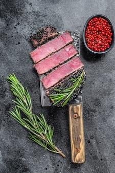 Smażone plastry stek z tuńczyka rybnego na tasaku do mięsa. czarne tło. widok z góry.