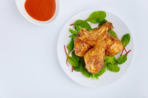 Smażone podudzia z kurczaka z pikantnym sosem na białym tle. widok z góry.