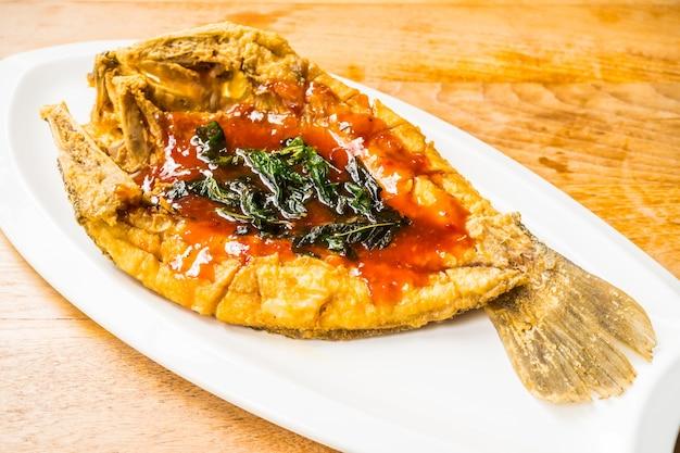 Smażone ryby okoń morski w białej tablicy z sosem pikantne i słodkie