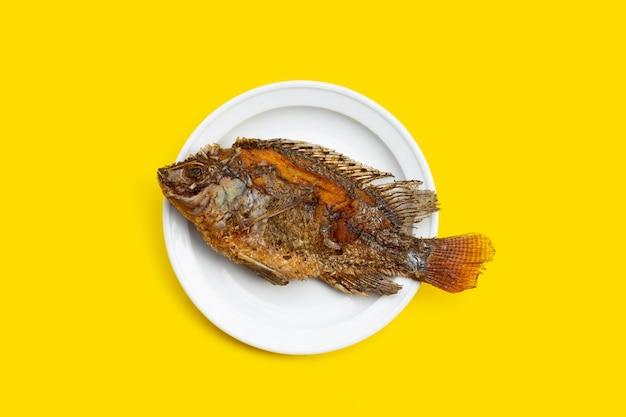 Smażone ryby w białej płytce na żółtym tle.