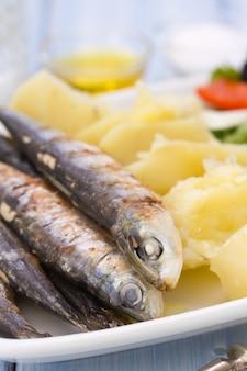Smażone sardynki z gotowanym ziemniakiem i sałatką na białym talerzu na niebieskim drewnie