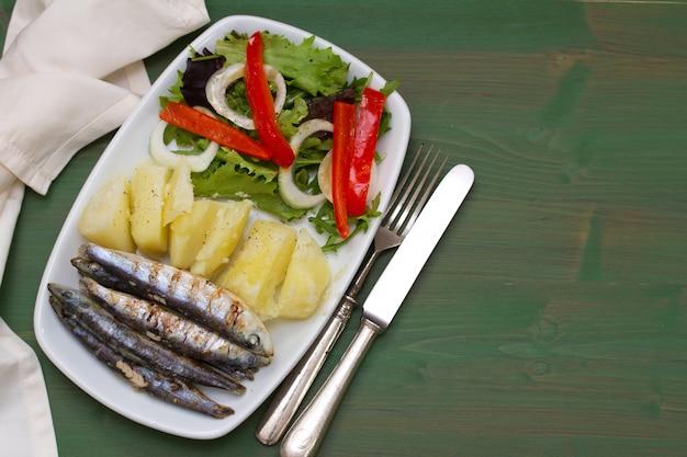 Smażone sardynki z gotowanym ziemniakiem i sałatką na białym talerzu na zielonym drewnie
