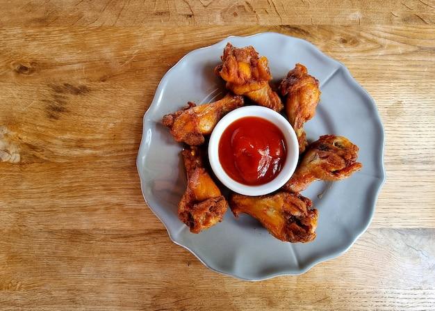 Smażone skrzydełka kurczaka z sosem pomidorowym na drewnianym stole