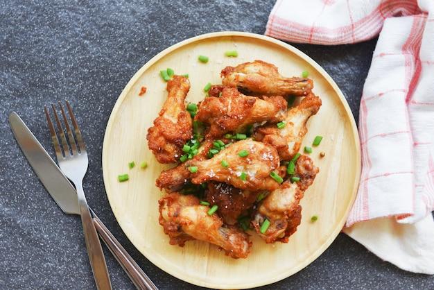 Smażone skrzydełka z kurczaka chrupiąca sól na drewnianym talerzu z nożem widelcowym w stole - pieczony kurczak z grilla