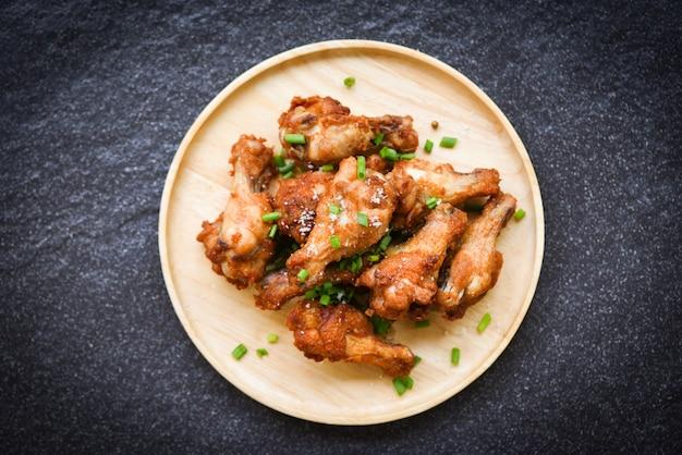 Smażone skrzydełka z kurczaka na drewnianym talerzu z solą i szczypiorkiem, widok z góry, pieczone skrzydełka z kurczaka bbq, skrzydełka chrupiące