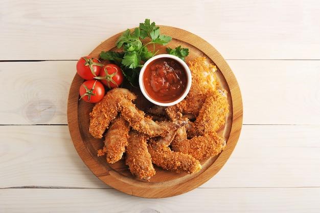 Smażone skrzydełka z kurczaka panierowane z keczupem, pomidorem i natką pietruszki