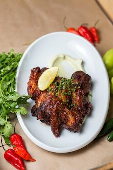 Smażone skrzydełka z kurczaka przyozdobione pokrojoną w kostkę zieloną cebulą, sosem i plasterkiem cytryny