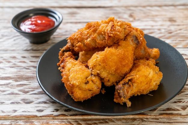 Smażone skrzydełka z kurczaka z keczupem, niezdrowe jedzenie