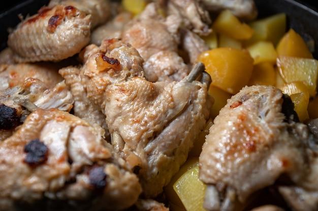 Smażone skrzydełka z kurczaka z ziemniakami gotuje się na patelni, zbliżenie z małą głębią ostrości