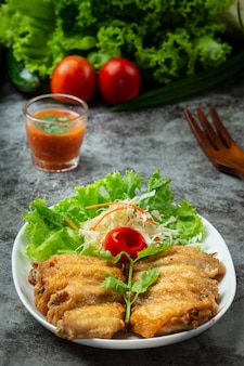 Smażone skrzydełka z sosem rybnym, pięknie udekorowane zioła i podawane.
