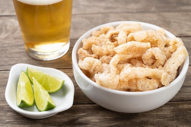 Smażone skwarki wieprzowe na białej misce z cytryną i piwem na drewnianym stole.