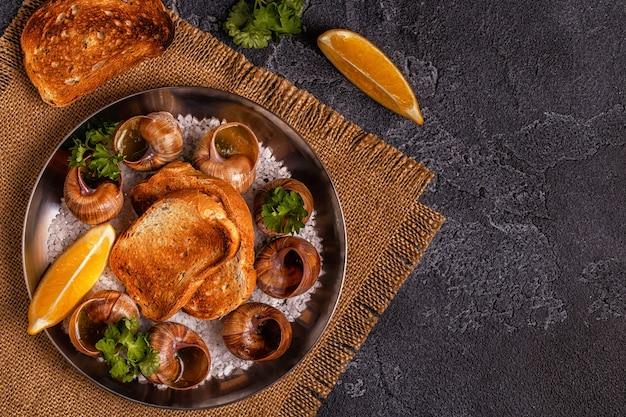 Smażone ślimaki z cytryną, bagietką i natką pietruszki