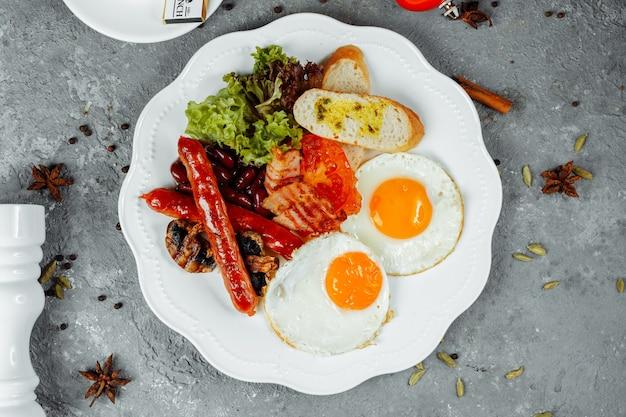Smażone śniadanie z boczkiem, kiełbasą i fasolką po bretońsku.