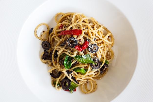 Smażone spaghetti chrupiący boczek i suszone chili na białym talerzu