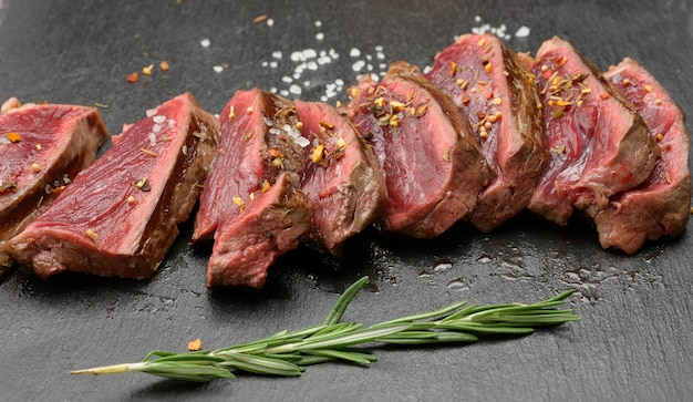 Smażone steki wołowe pokrojone na kawałki na czarnej desce, stopień wypieczenia rzadki z krwią, z bliska
