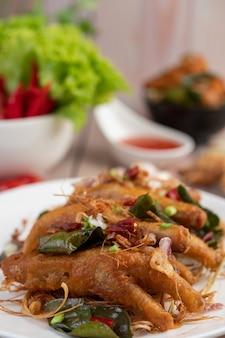 Smażone stopy kurczaka z ziołami na białym talerzu i sosie do zanurzania.
