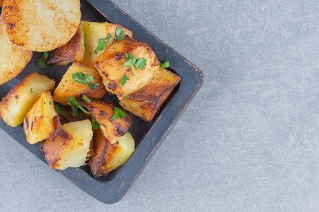 Smażone świeże ziemniaki w czarnej tablicy na szarym tle.