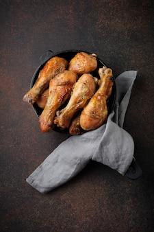 Smażone szpiczaste podudzie kurczaka na żeliwnej patelni na ciemnym betonie