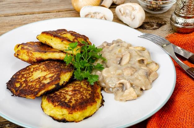 Smażone tarte placki ziemniaczane z sosem grzybowym.