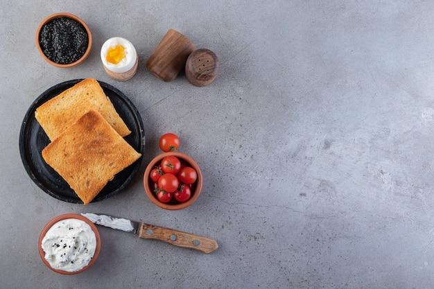 Smażone tosty z masłem i czerwonymi świeżymi pomidorkami cherry umieszczonymi na tle.