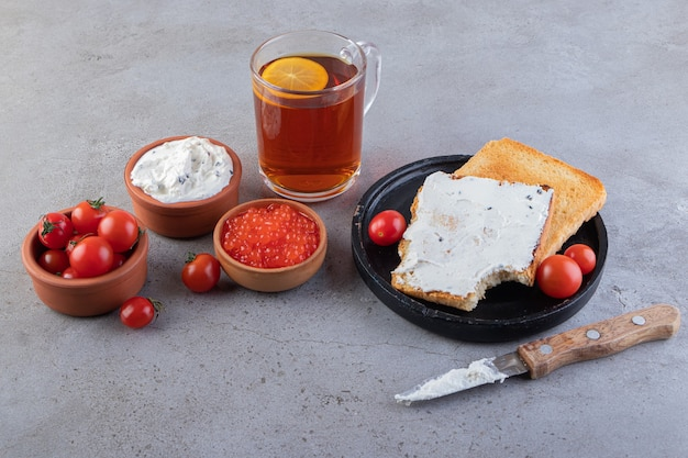 Smażone tosty z masłem i czerwonymi, świeżymi pomidorkami koktajlowymi ułożonymi na marmurze.