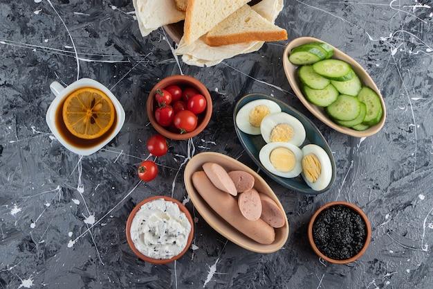 Smażone tosty ze świeżymi czerwonymi pomidorkami cherry umieszczonymi na marmurowym stole.