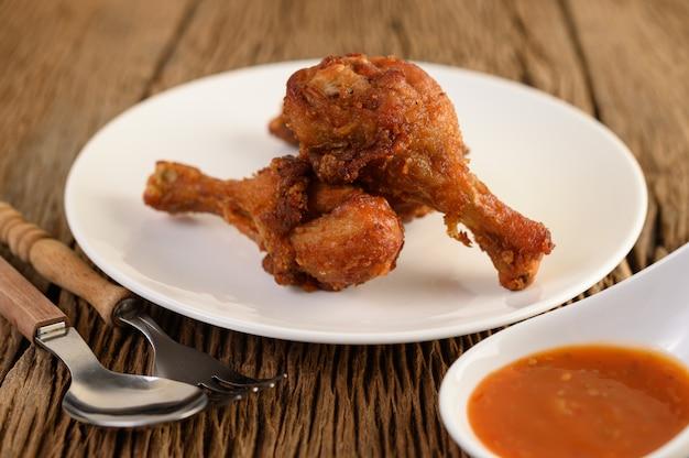 Smażone udka z kurczaka na białym talerzu z łyżką, widelcem i sosem.