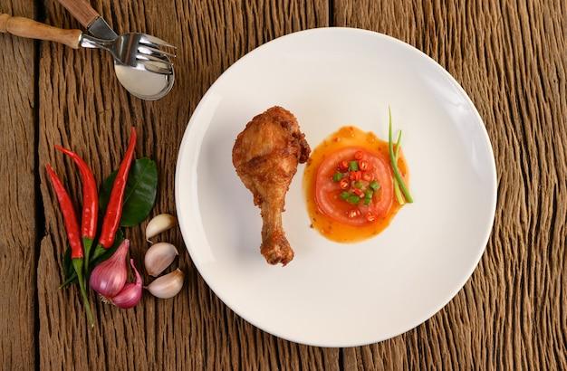 Smażone udka z kurczaka na białym talerzu z sosem i czosnkiem, szalotka, chili.