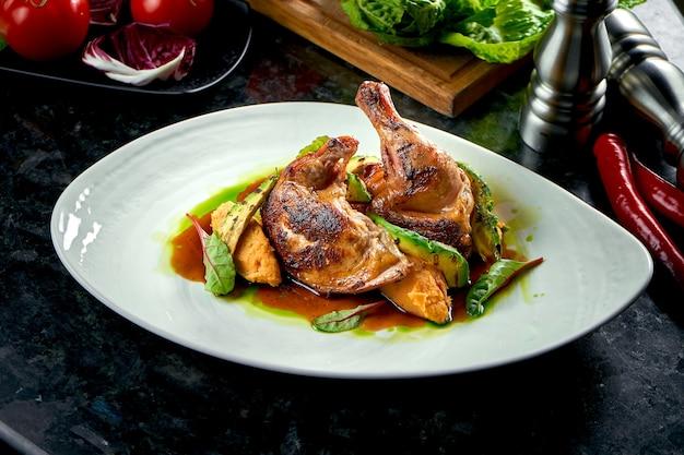 Smażone udka z kurczaka w żółto-zielonym sosie udekorowane puree ziemniaczanym i avakodos, podawane na białym talerzu. jedzenie w restauracji. danie mięsne