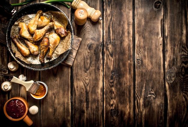 Smażone udka z kurczaka z sosem pomidorowym. na drewnianym stole.