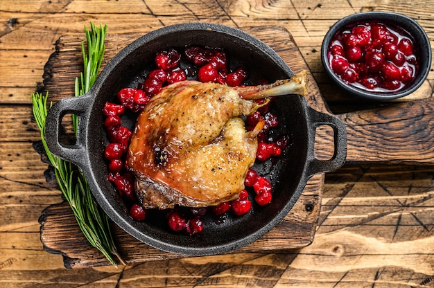 Smażone udko z kaczki z sosem cranberrie na patelni. drewniane tła. widok z góry.
