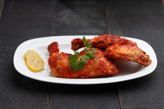 Smażone udko z kurczaka lub pałeczka do smażenia na ostro smażonego indyjskiego kurczaka z czarnym tłem