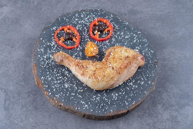 Smażone udko z kurczaka na kawałku drewna.