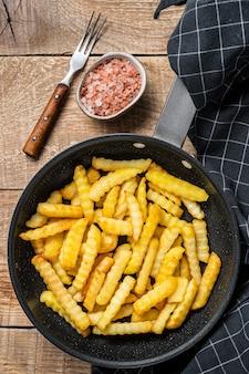 Smażone w głębokim tłuszczu crinkle french frytki ziemniaczane na patelni