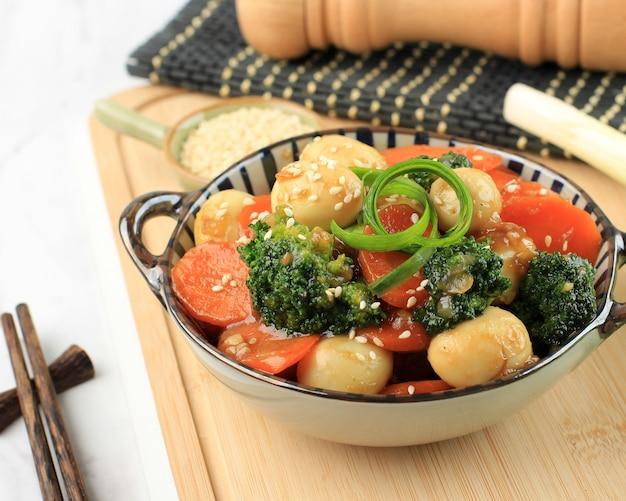 Smażone warzywa i jajko przepiórcze w sosie ostrygowym (telur puyuh saus tiram), na wierzchu dodaj ziarno sezamu