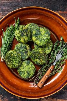 Smażone wegetariańskie burgery warzywne brokuły patty na rustykalnym talerzu. ciemne drewniane tło. widok z góry.