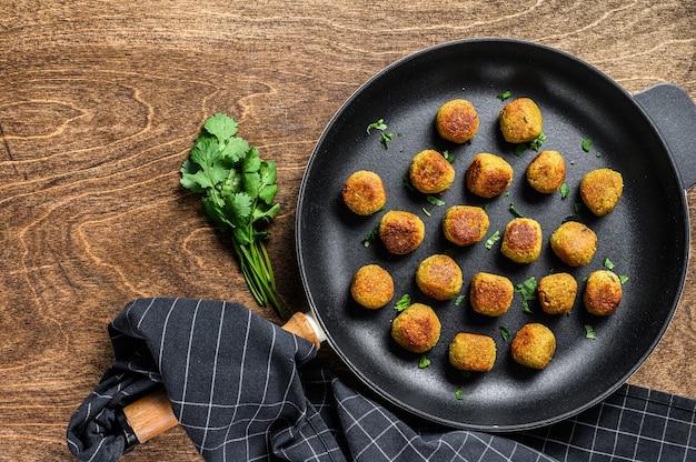 Smażone wegetariańskie falafele z przyprawionej ciecierzycy na patelni