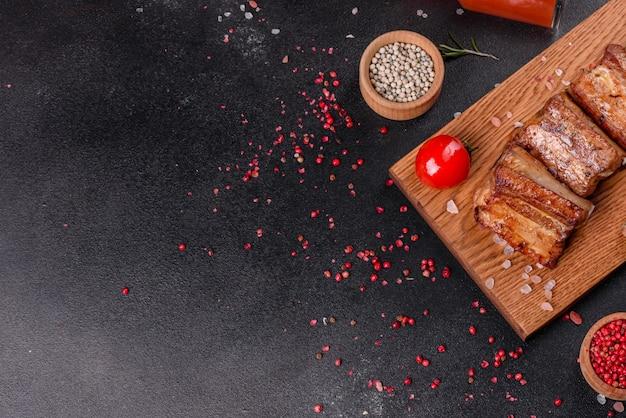 Smażone żeberka z rozmarynem, cebulą, sosem na betonowej powierzchni. ciemny stół. miejsce na tekst, miejsce