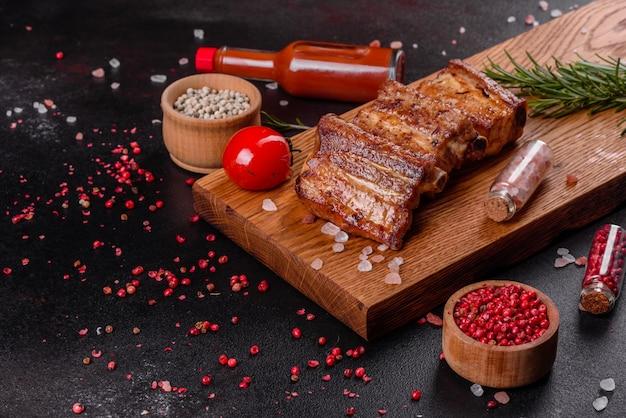 Smażone żeberka z rozmarynem, cebulą, sosem na betonowym tle. ciemny stół. miejsce na tekst, miejsce